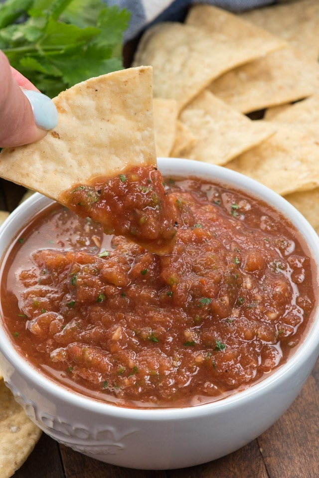 chip being dipped in salsa in white bowl