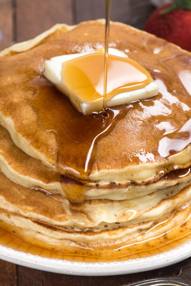 close up of stack of fluffy pancakes with syrup