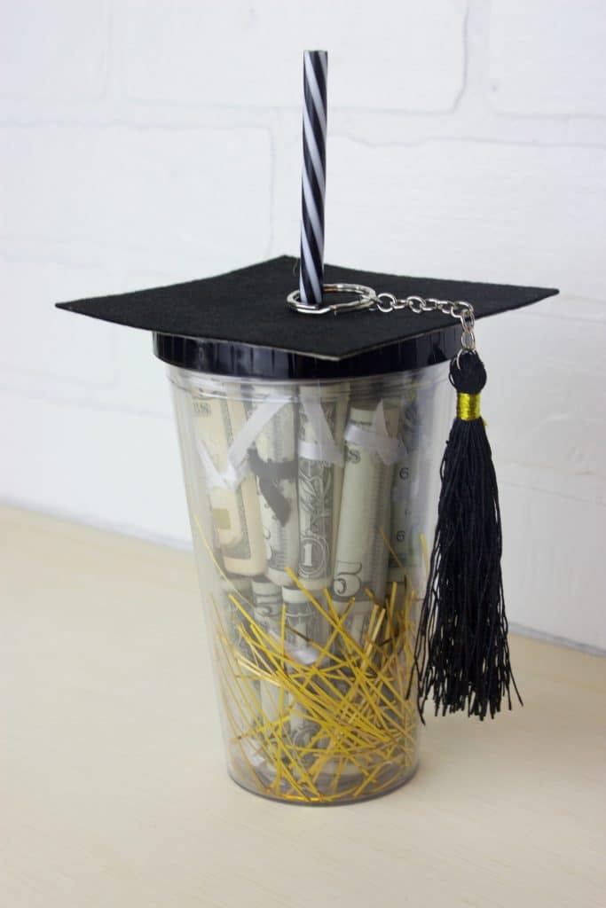 a jar filled with rolled up money and on top is a graduation hat covering the opening of the jar