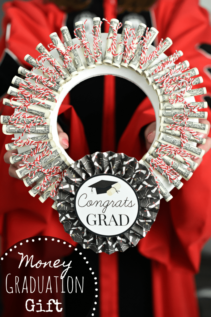 "A wreath made of rolled up dollar bills tied with red and white yarn and an emblem at the bottom that says ""congrats Grad"""