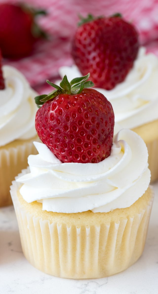 Strawberry Shortcake Cupcakes with white frosting and a strawberry on top