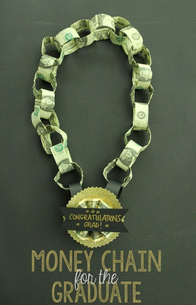 A medal that says congratulations grad and the par that goes around your neck is a chain of dollar bills