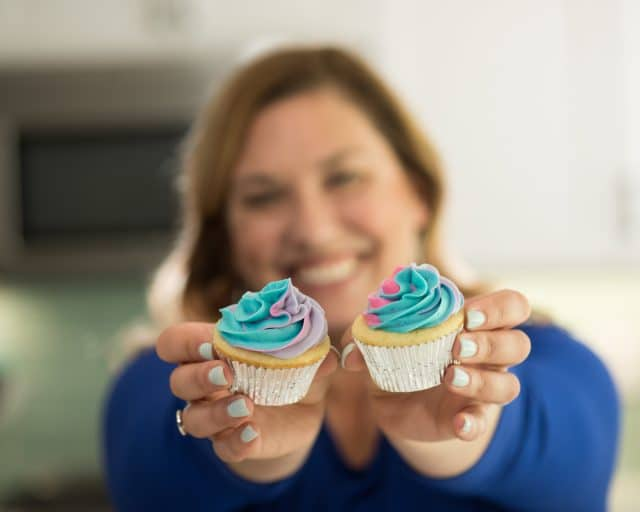 woman holding two cupcakes