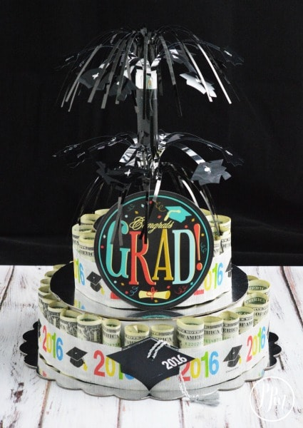 "It looks like a two tiered cake. Each tier is made up of rolled up money and there is a round circle cut out that says ""grad"" and some black decoration protruding from the top that looks like fireworks"