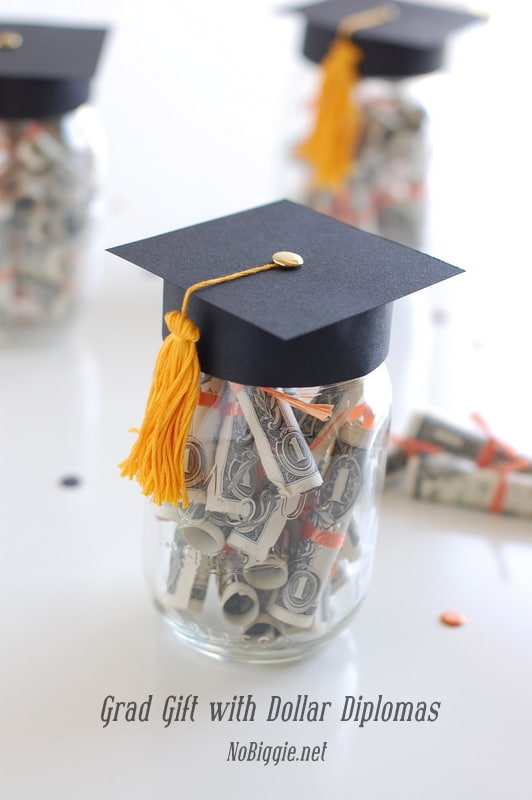 a jar filled up with rolled up money and the top of the jar is covered with a graduation hat