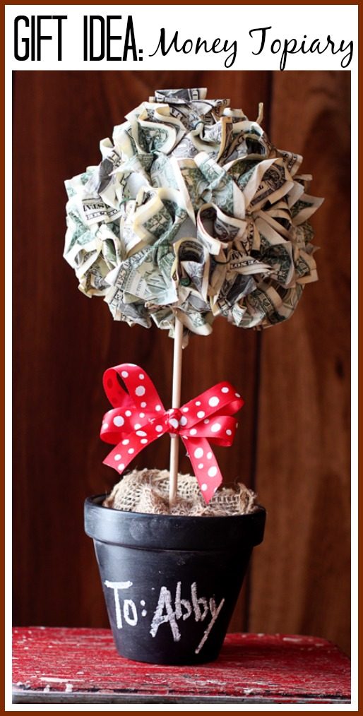 A plant made out of money crumpled up and a stick going into a plant pot