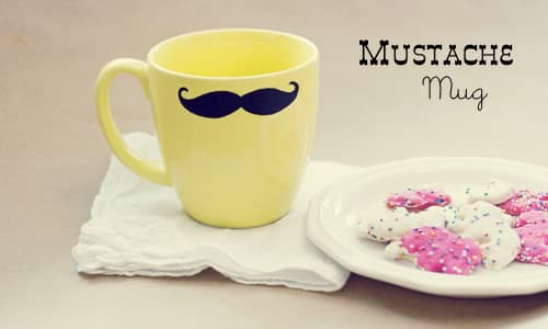 a mug with a mustache on it next to a white plate with cookies on it