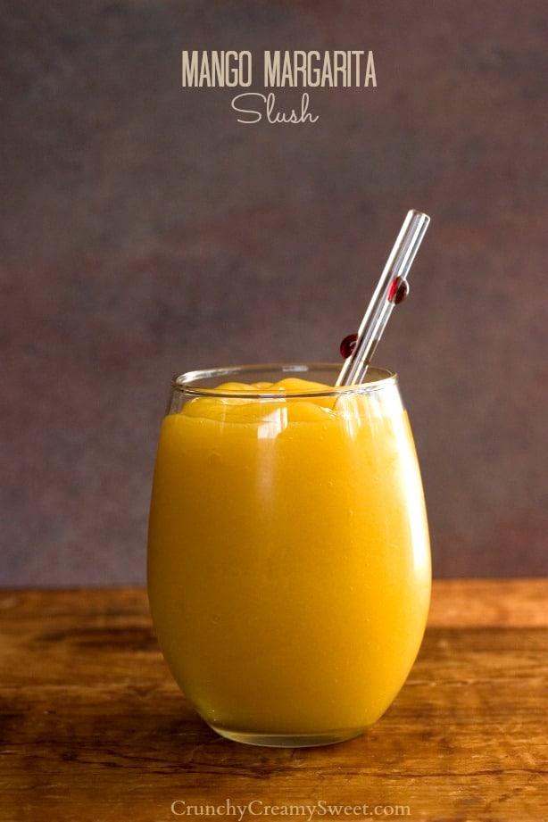 Mango margarita slush in a small glass with a straw