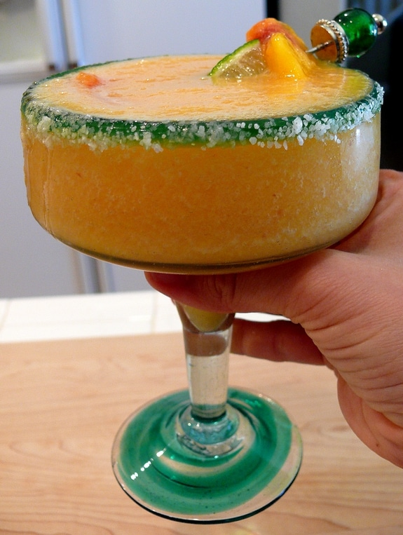 person holding a frozen peach margarita in a stemmed glass