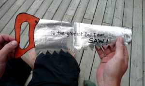 "a saw made out of tin foil and a red paper handle that says ""to the greatest Dad i ever saw"""