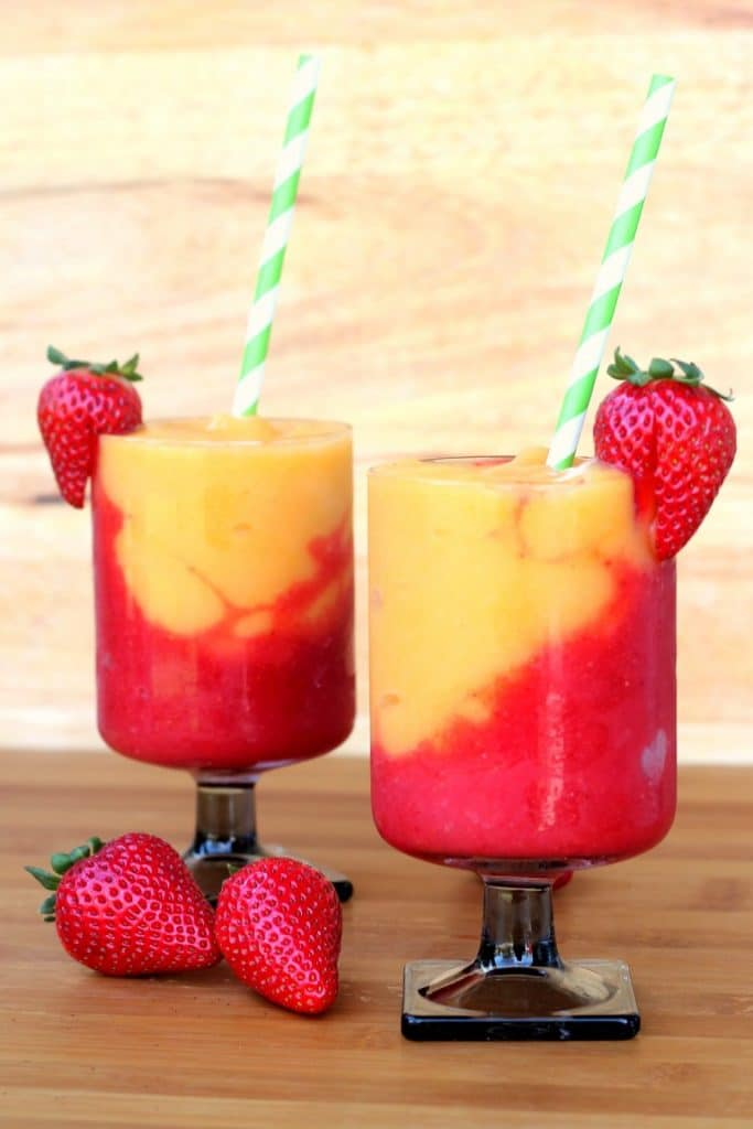 2 strawberry and peach wine slushies in short stemmed glasses with straws