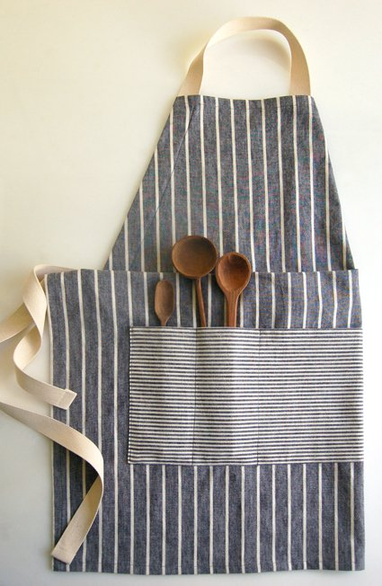a chef's apron with three wood spoons in a pocket