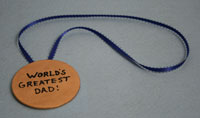 "a medal that says ""worlds greatest Dad"""