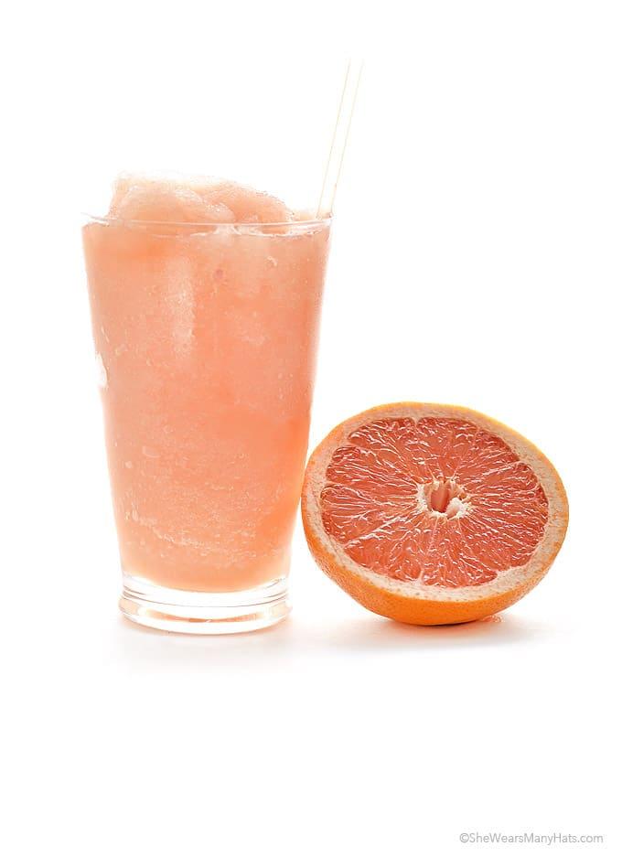 grapefruit slushie in a glass next to a half of a grapefruit