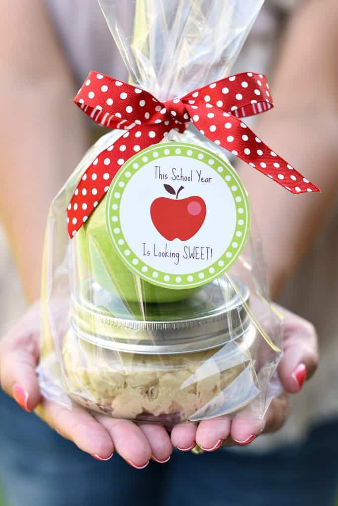 a jar with pie crust and a green apple wrapped in plastic with a tag tied to it with red and white ribbon