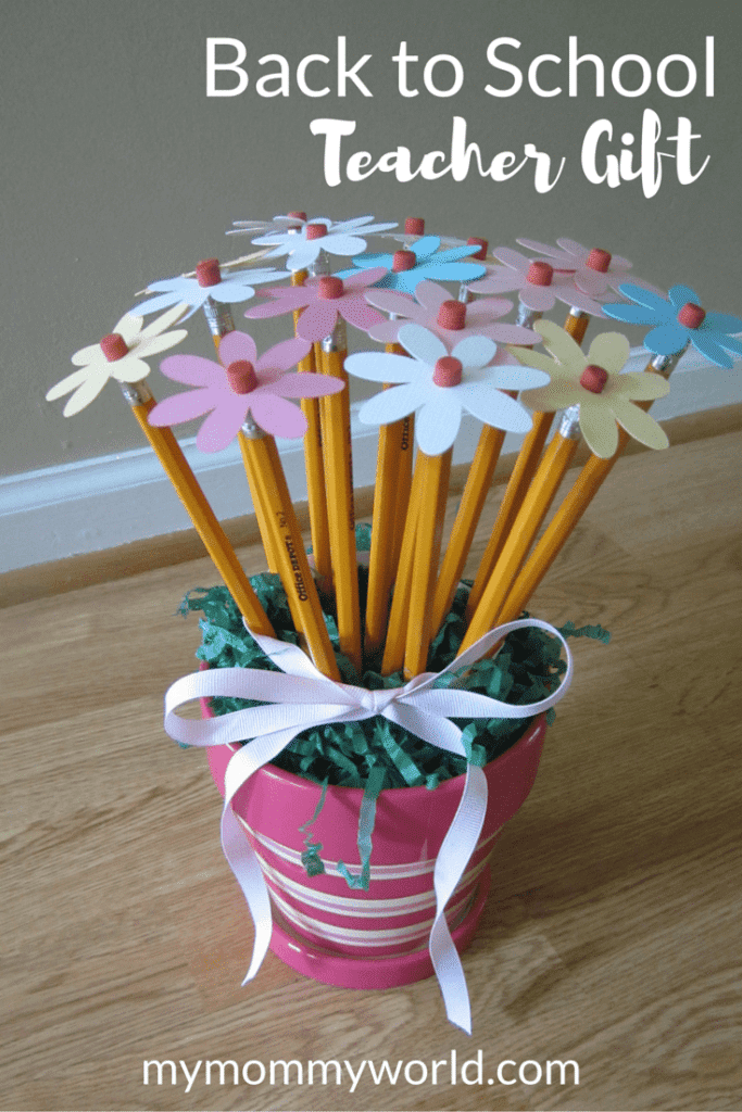 a plant pot that is pink and is filled with pencils that have cut out flower tops around the erasers