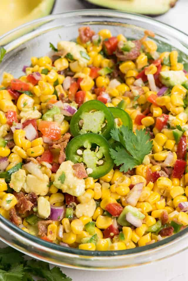 Corn Salad close up in a large glass bowl with jalapenos on top