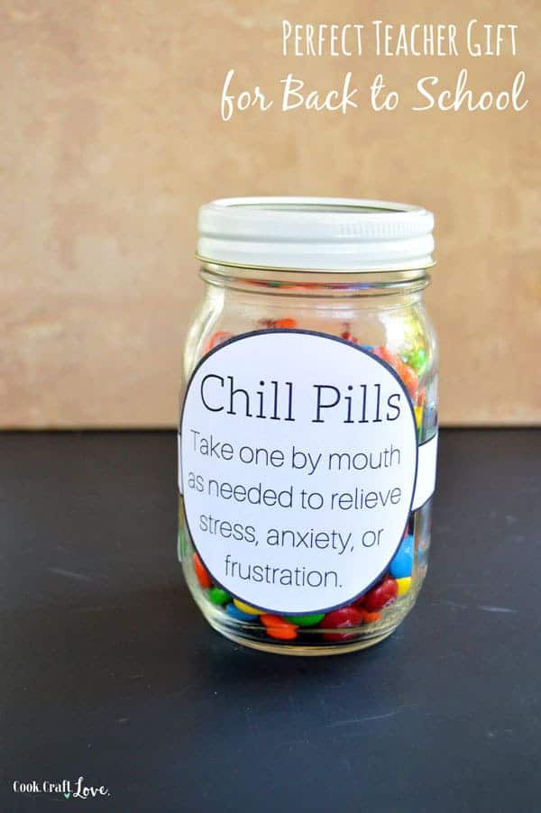 a clear glass jar filled with M and M's and a sticker put on the jar with writing