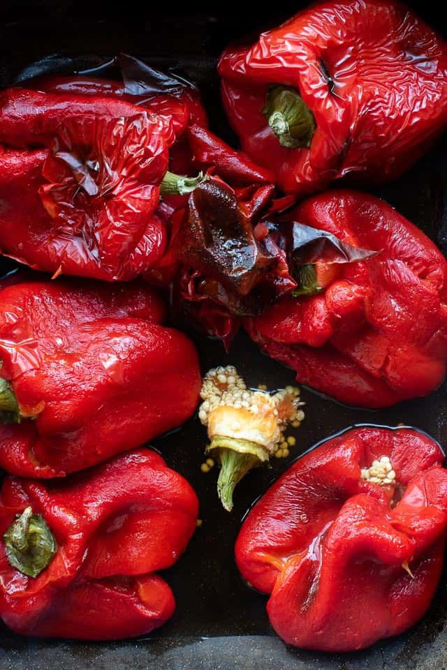 Half peeled Roasted Red Peppers in black baking pan