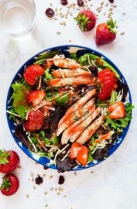 Overhead image of Strawberry salad in a blue and white bowl.