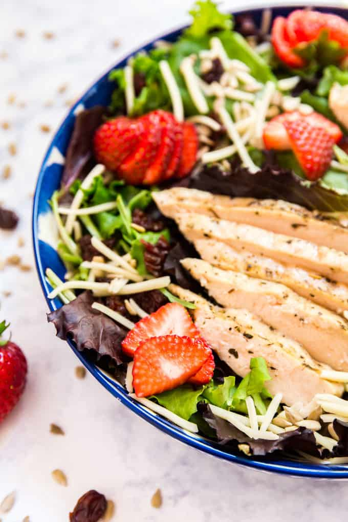 A close up image of the grilled chicken on a strawberry salad.