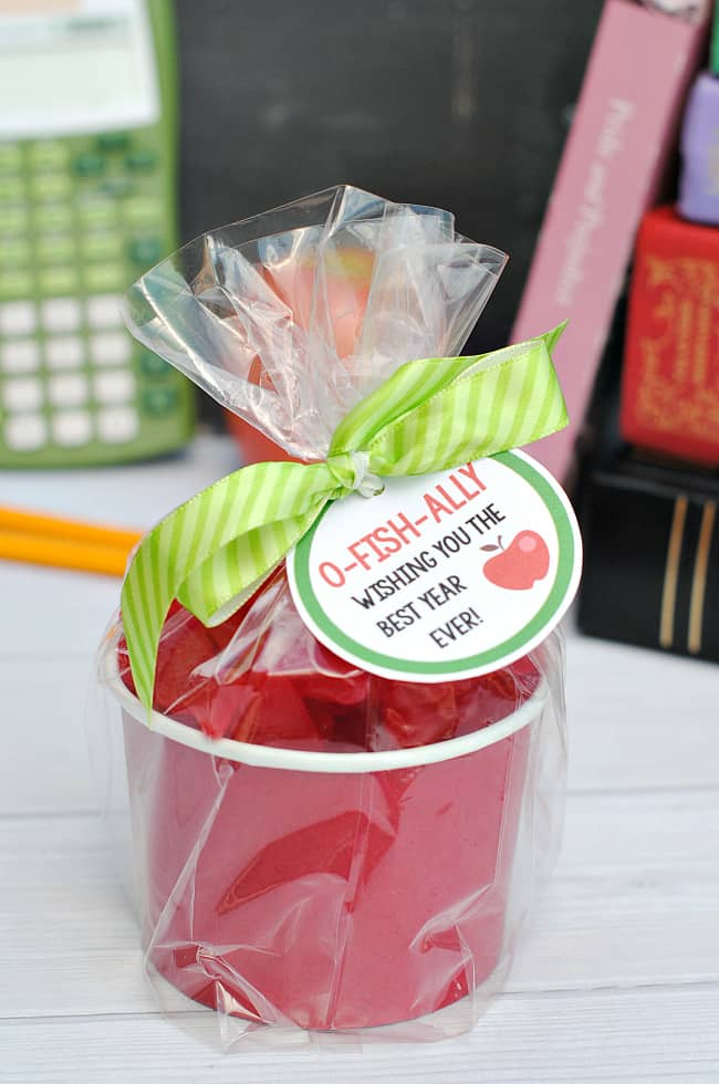 a red paper bowl filled with candy and a tag tied to the top with writing
