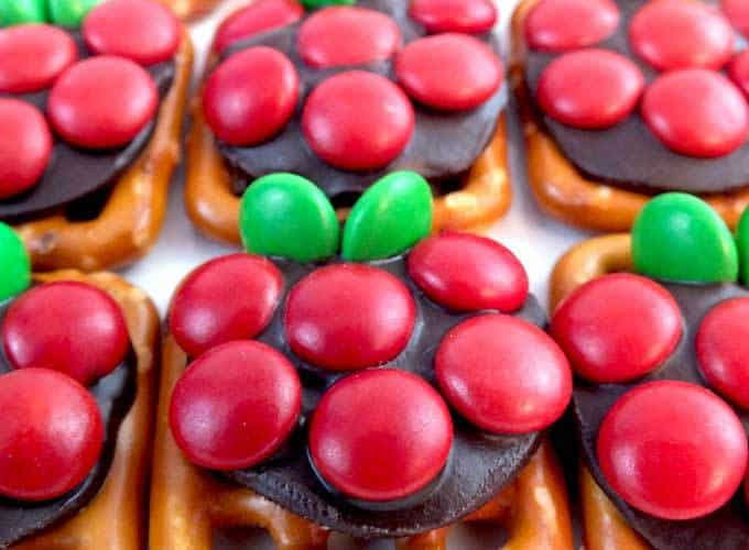 pretzels with chocolate rounds and red and green candy that make them look like apples