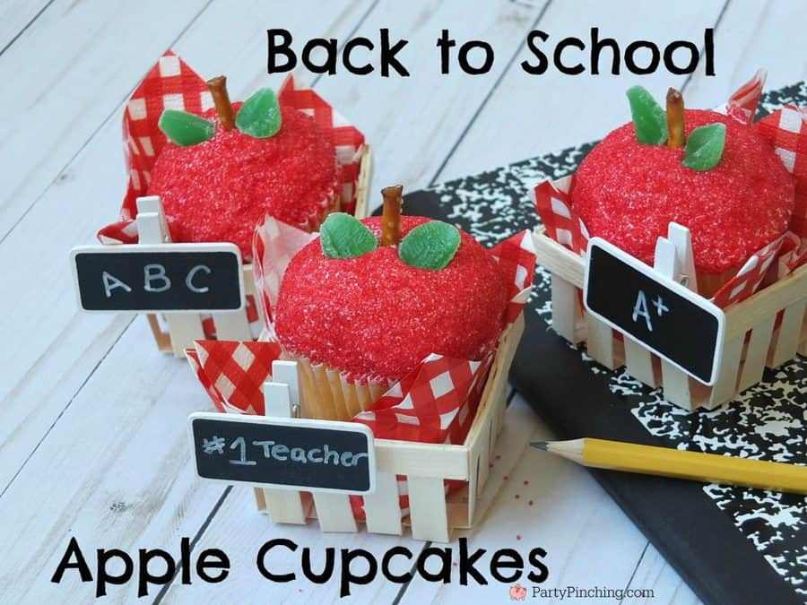 three little containers with cupcakes in them that look like apples with writing