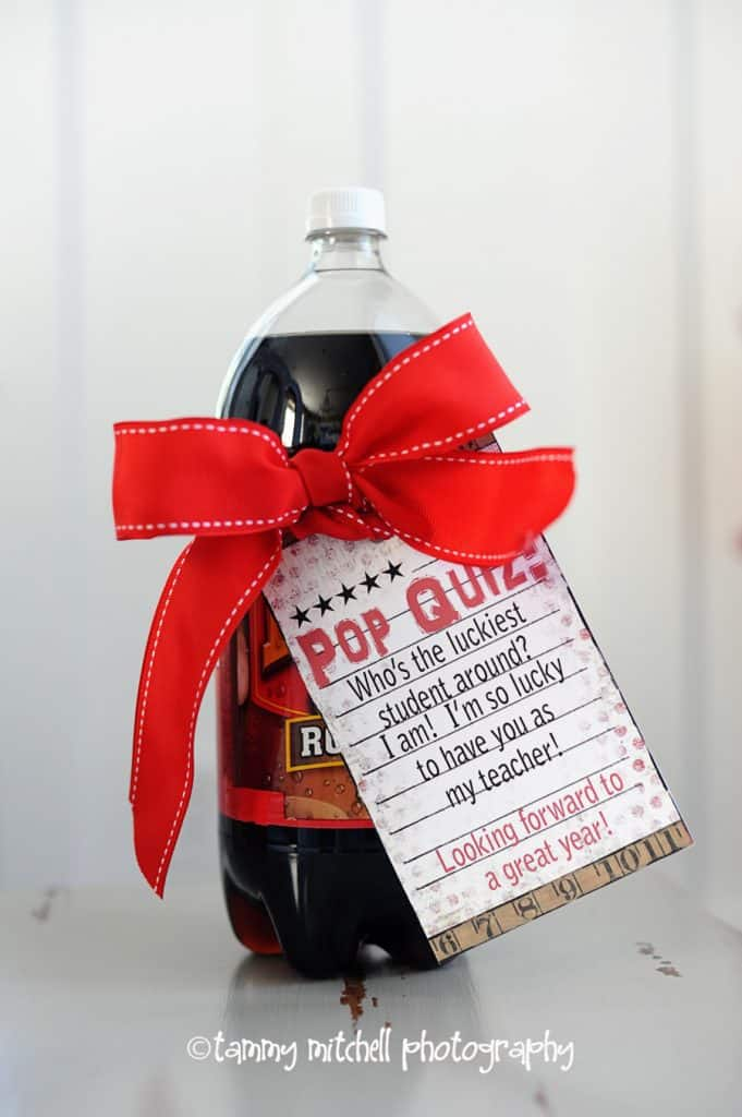 a two liter bottle of root beer with a tag tied around it with a red bow with writing
