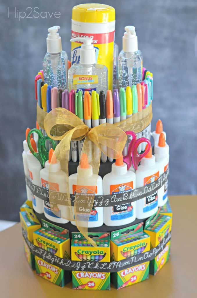 a tiered cake made out of boxes of crayons, elmers glue, sharpies and hand sanitizer
