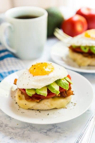 A side angle of the California Breakfast Stack showing the egg on top of the avocado slices, sliced tomato, bacon, cheese and english muffin.