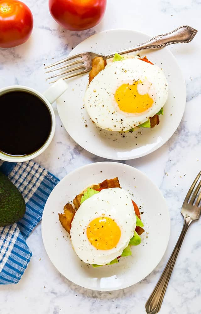 Overhead image of two California Breakfast stacks on a white marble table with forks and coffee
