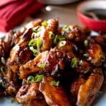 Pile of honey baked chicken wings on blue plate