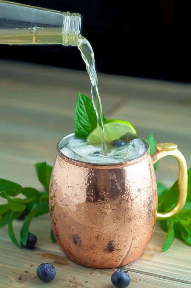 a bottle of ginger beer being poured into a blueberry maple Moscow mule in a copper mug