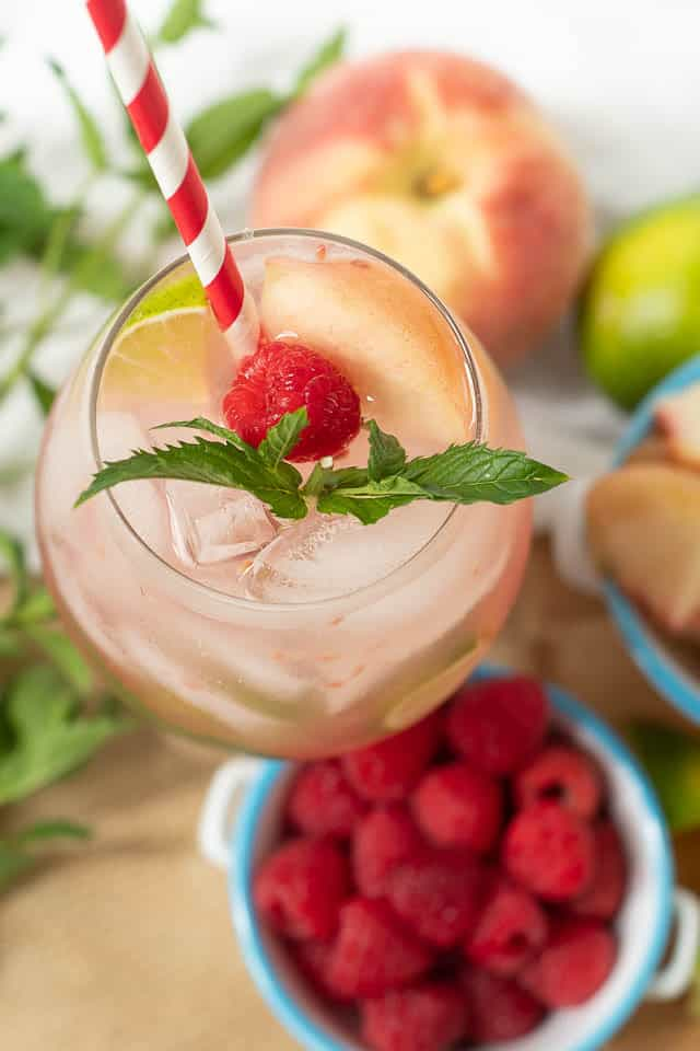 an overhead, close up shot of a Peach Raspberry Mojito glass with a red straw sticking out