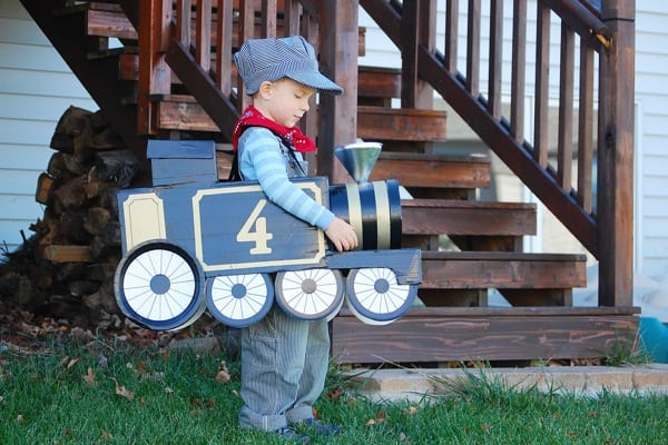 Boy carrying a small blue train