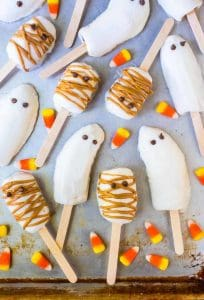 ghost and mummy pops on a cookie sheet