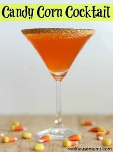 Candy Corn Cocktail in a martini glass with candy corn on the table below the glass with writing
