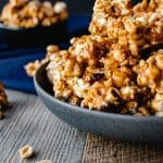 Homemade caramel corn in a grey bowl on blue cloth. smaller black bowl of caramel corn in background caramel corn and nuts on wooden table. close