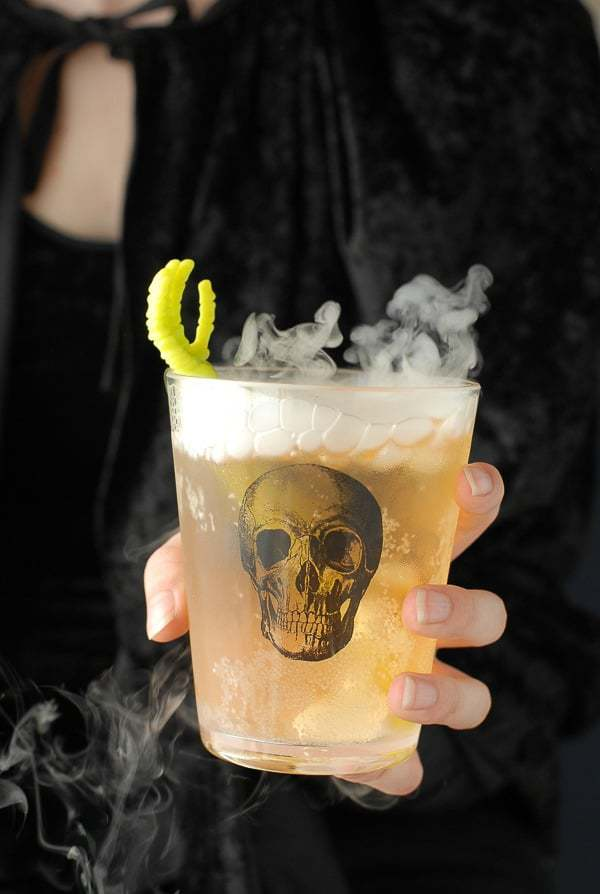 The Grave Digger cocktail in a glass with a skull on it and smoke coming out the top