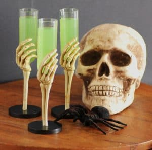 Embalming Fluid cocktail being held by three skeleton hands