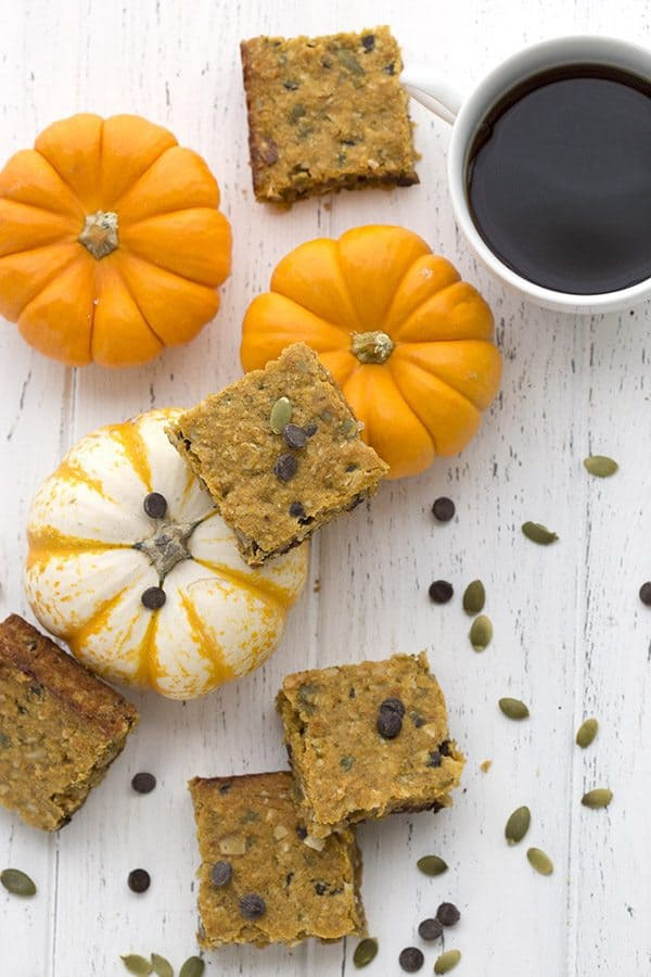 Pumpkin Oatmeal Breakfast Bars on a wooden board with small pumpkins and some pumpkin seeds