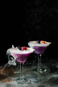 The Witches Heart cocktails in martini glasses on a dark counter. The liquid is purple