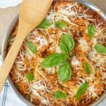an overhead shot of easy skillet lasagna in a pan with a wooden spoon resting on top