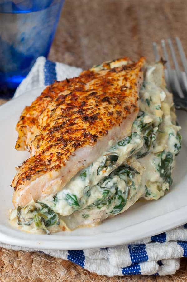 spinach artichoke chicken on a small white plate with a water glass in background