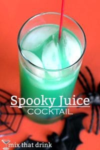 Spooky Juice cocktail which is green in a glass and a red background with spiders and a bat