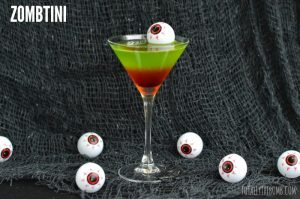 Zombtini cocktail with a fake eyeball floating in it and other fake eyeballs on the table below