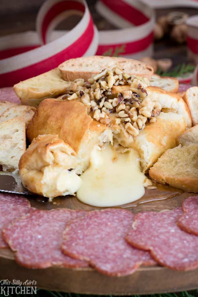 Baked Brie with Walnuts and Honey cut open sitting on a board with salami in front of it