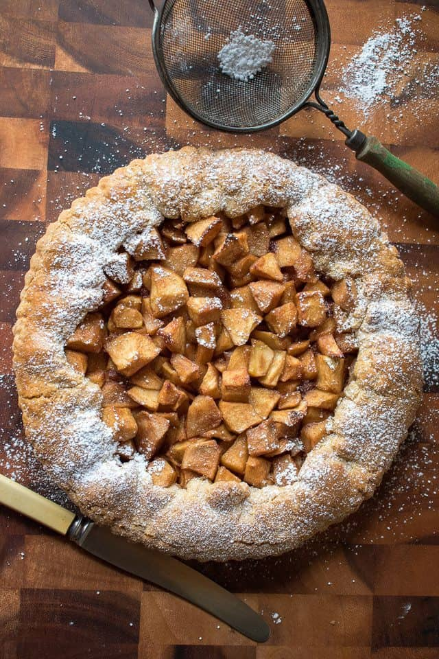 Open apple tart on wooden table with vintage knife and sifter