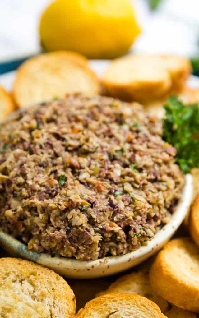 A close up image of a bowl of Olive Tapenade with sliced baguette around it.